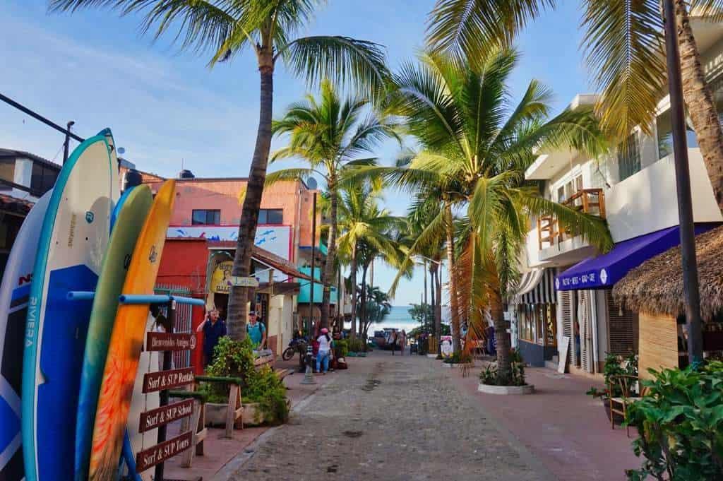 Der Weg zum Strand führt an Surfbrettern und Palmen in Sayulita vorbei